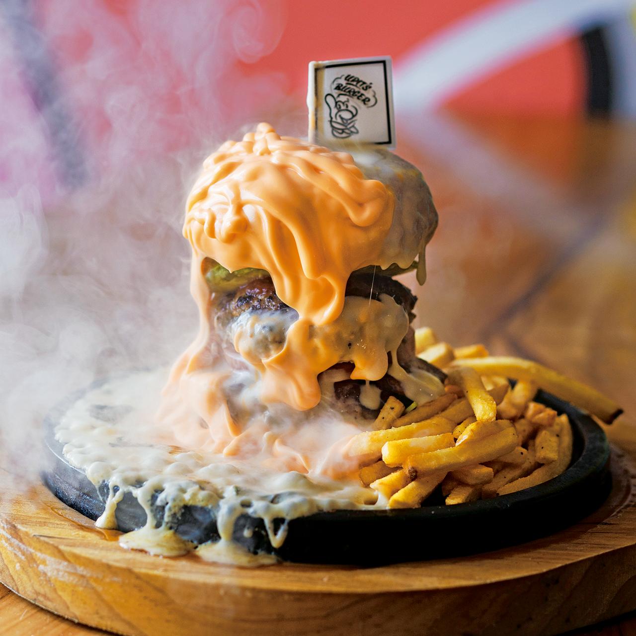 ナチュラルとチェダーのチーズ層が豪快に流れる名物バーガー・溶岩d e チーズバーガープレート1680円(税込)。仕上げの炎でテンションMAX