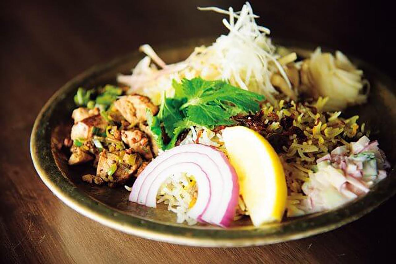 アチャールやライタ、ピクルスなど副菜を混ぜると、ひとすくいごとに味が変化していく。鯛出汁チキンビリヤニ(ハーフ)800円、マトンビリヤニ(ハーフ)800円の合い盛り。+麻婆豆腐200円(すべて税込)