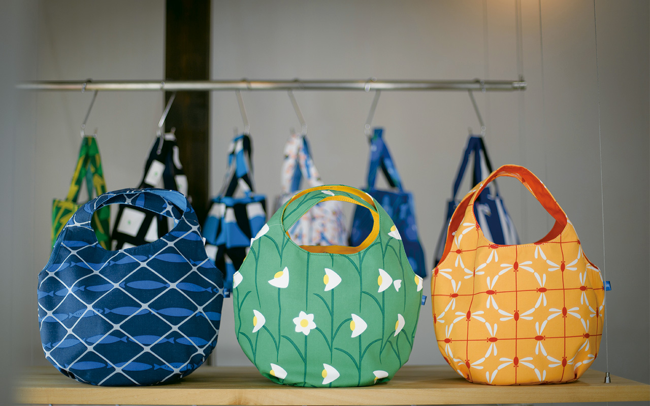 丸い月をイメージしたまんまるバッグ各7480円は、ちょっとしたお出掛けにぴったりのサイズ。今秋冬の新作デザインであるイワシ・水仙・赤とんぼの3タイプを用意