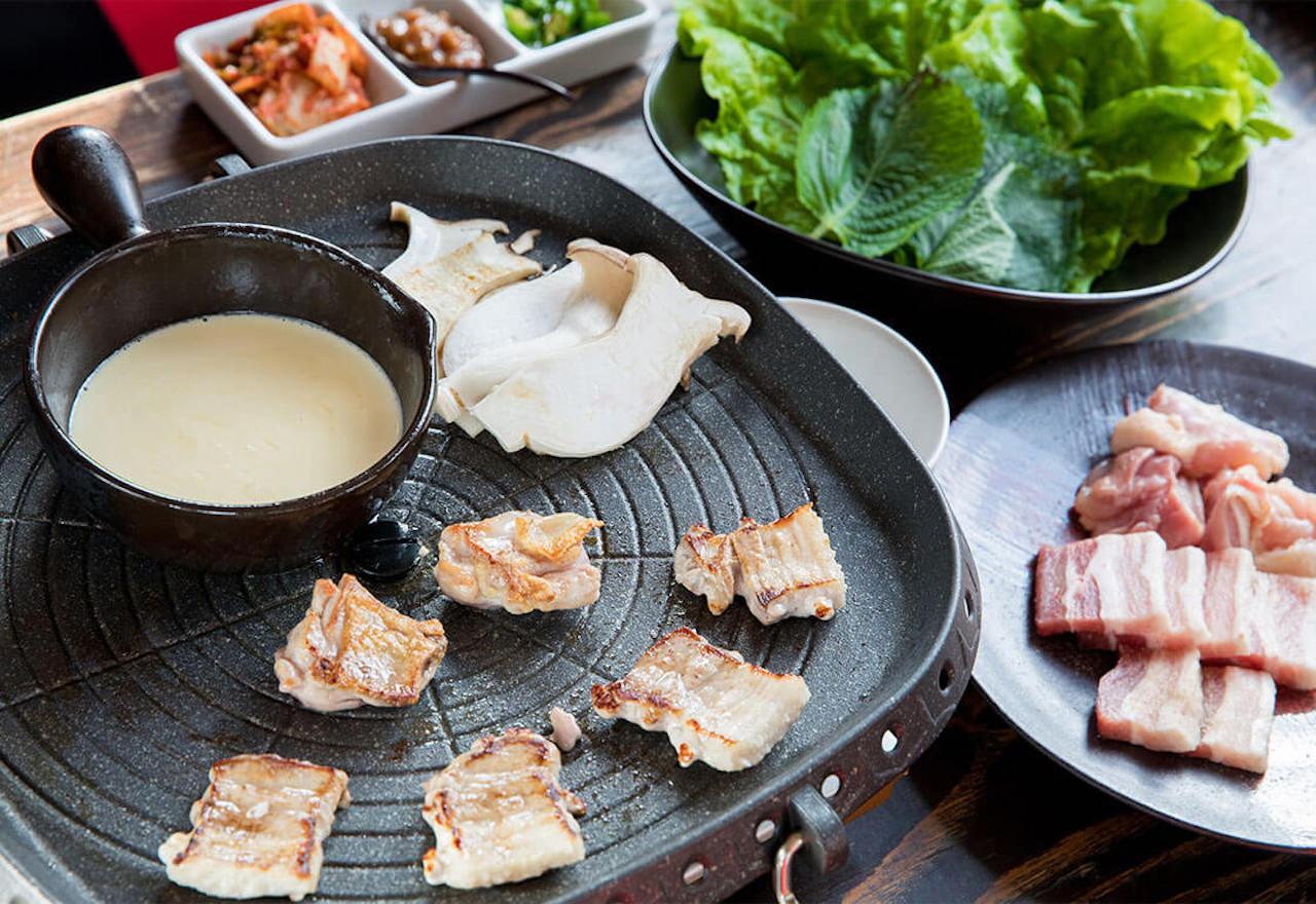近年、韓国で流行りのチーズフォンデュで味わうサムギョプサル1,500円。焼いた豚バラ肉と大山どりをチーズに絡め、サンチュや甘辛味噌のサムジャ、キムチを巻いてかぶりついて