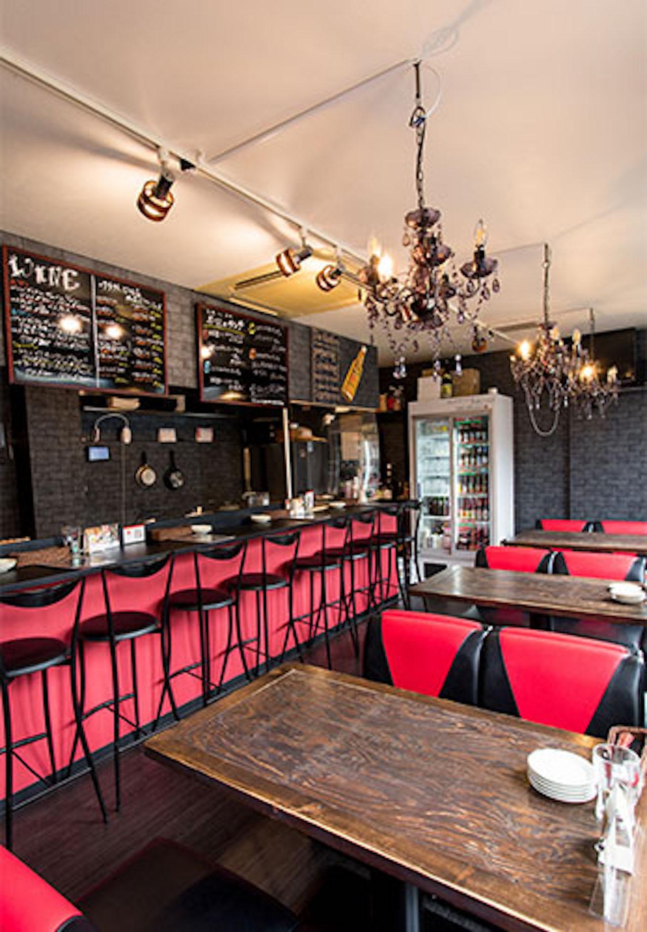 オープンキッチンなのでシェフとの会話も弾みそう。黒を基調に、木製のテーブル、鮮やかな赤とのコーディネートが印象的