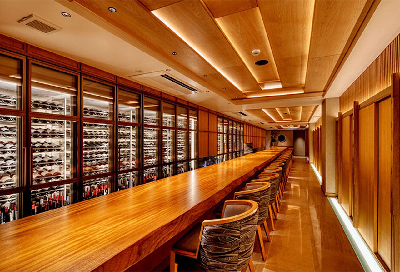 心地よい間接照明の店内には、幅90㎝、長さ18mもある圧巻のカウンターと西陣織が施された豪華な椅子がゆったり並ぶ