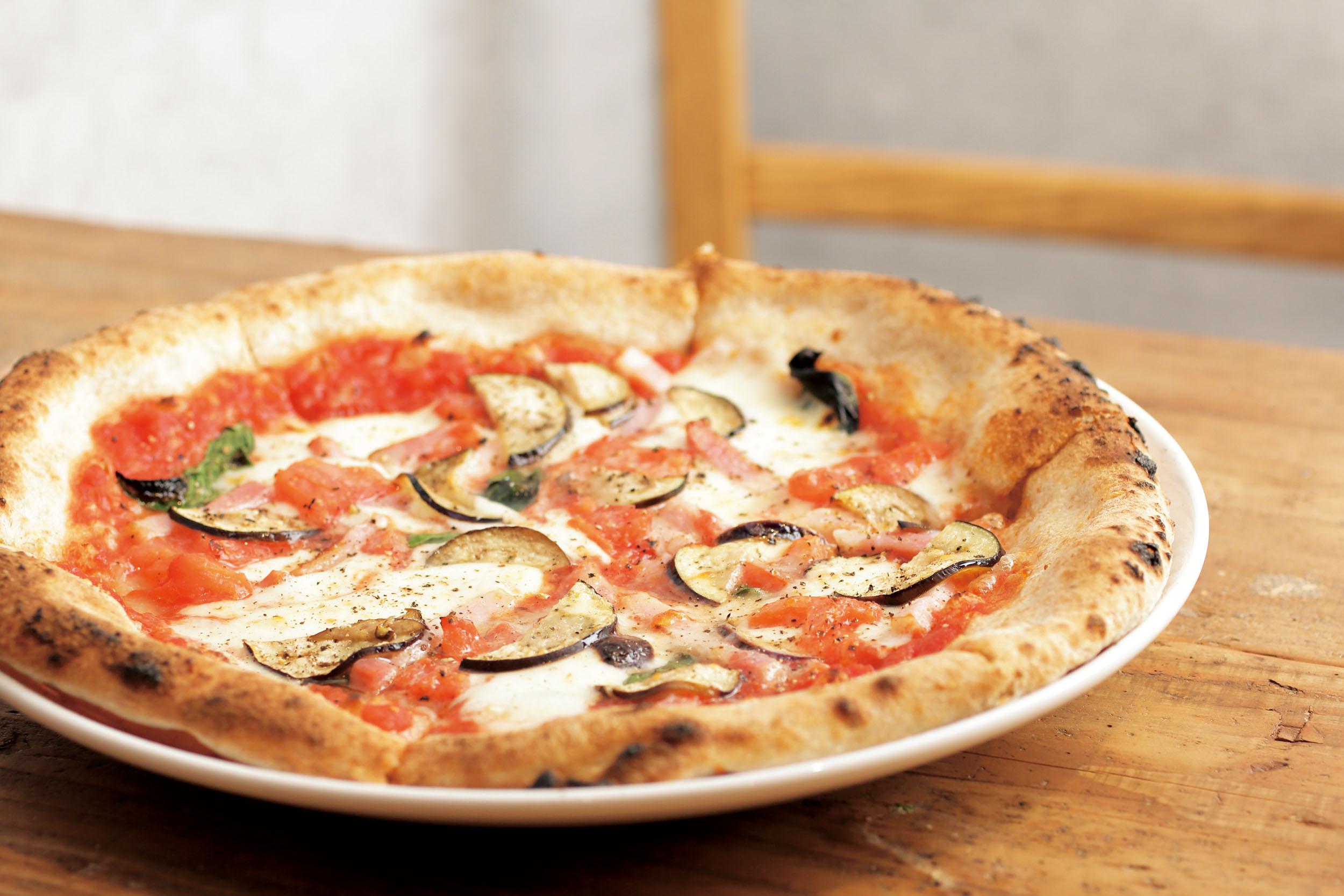 トマトとナスのピッツァ1540円<br /> 野菜をたくさん食べてほしいという店主の思いが詰まった一枚。さっぱりとしたトマトソースの上にナスを散りばめた、クセになる味わい。