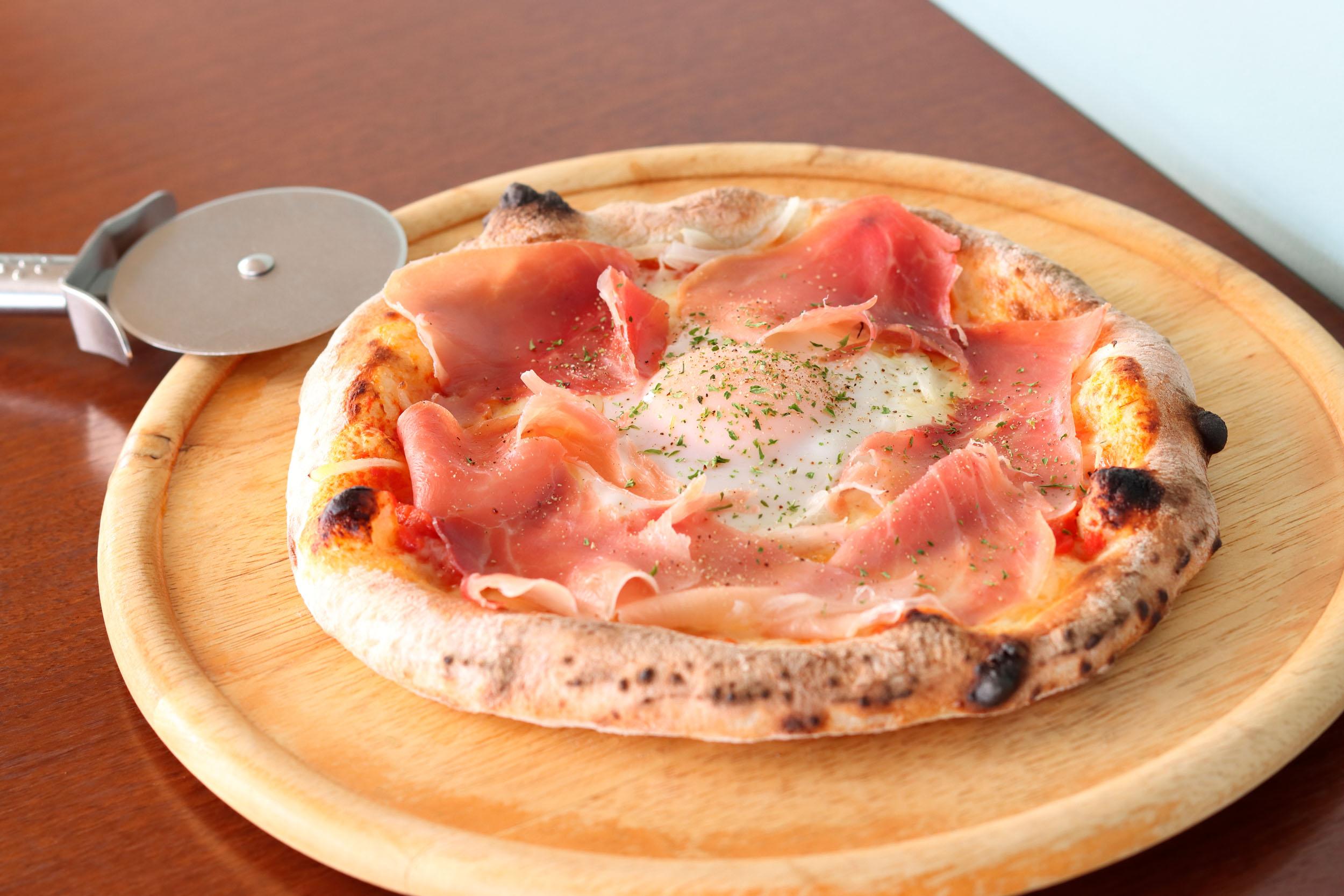 生ハムと半熟卵のピッツァ1485円<br /> オレガノが香るトマトソースにたっぷりの生ハムを散りばめた人気メニュー。ランチセットはサラダ&前菜・ドリンク・デザート付き
