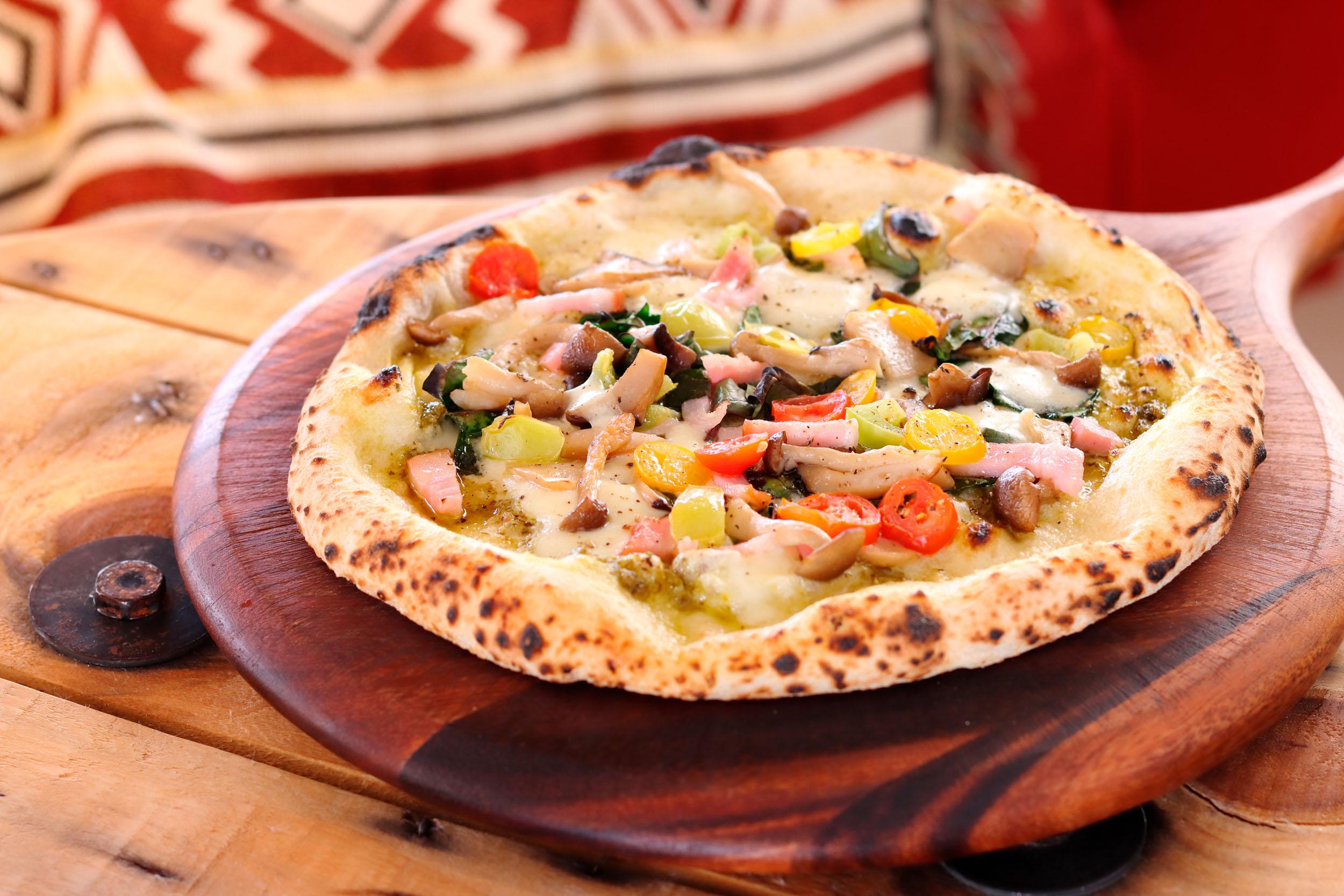 旬の野菜 pizza 1400円。ジェノベーゼソースをベースに、ミニトマトやほうれん草、キノコ、ベーコンなど盛りだくさん。グラナパダーノチーズをアクセントに