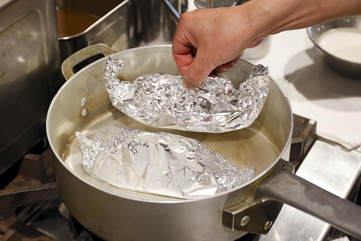 ③<br /> アルミホイルの奥と手前の部分を合わせ、隙間ができないよう合わせて折り返す。包んだホイルをフライパンに移し、水を100cc入れ、蓋をして弱火で10分ほど加熱する。