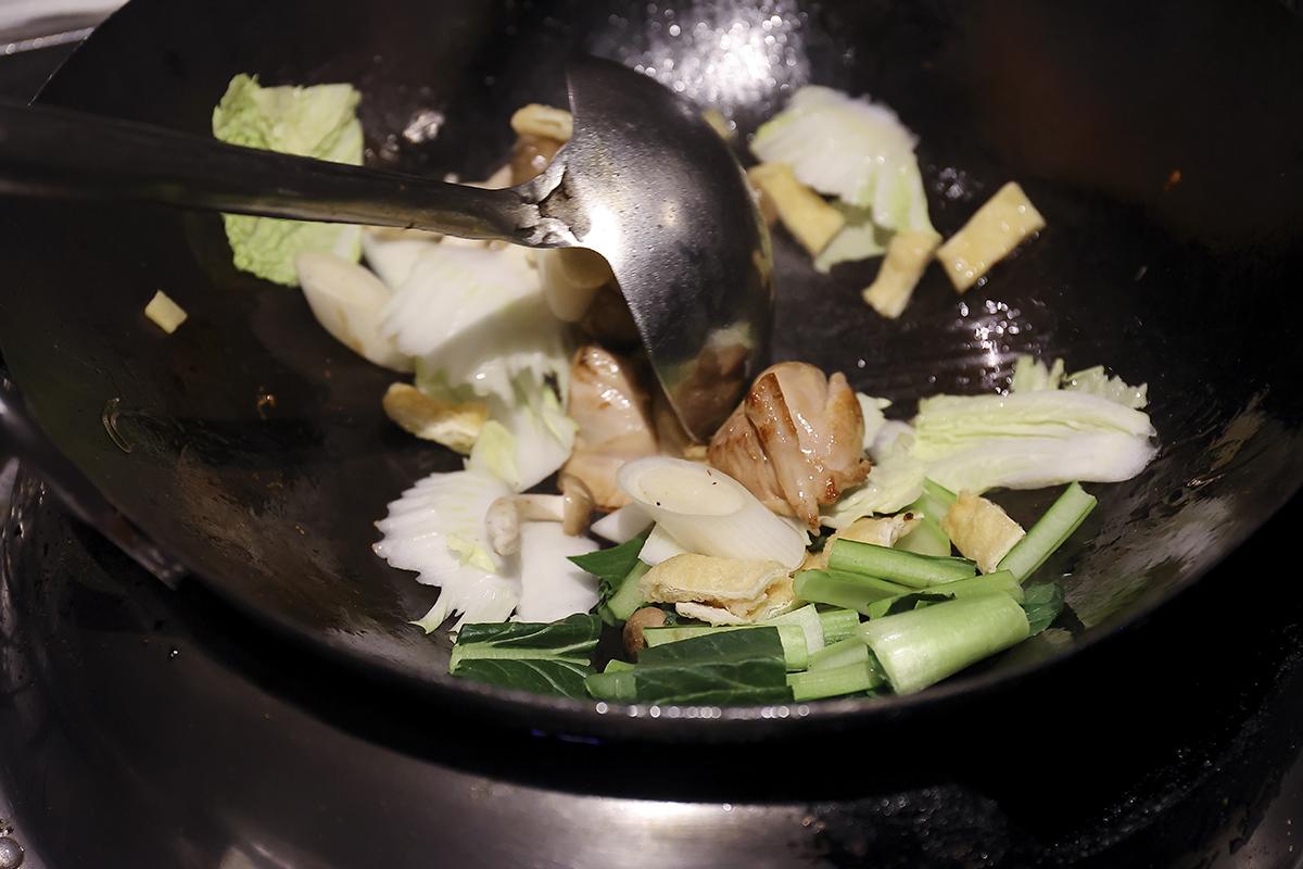 ②<br /> フライパンにサラダ油を入れ、中火にかけてよく熱したところに鶏もも肉、白ネギとショウガ入れ、表面がカリッと香ばしくなるまで炒める。白菜、小松菜、しめじ、筍、うすあげを加えて炒める。水と鶏ガラスープを加えて煮る。