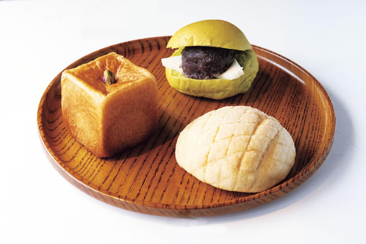 右上から時計回りに。有機小豆のあんことバターたっぷりのあんバタ220円。クッキー生地とふわふわパン生地のバランスが絶妙のクリーム入りメロンパン160円。キューブ型ブリオッシュ280円は、ピスタチオクリームを絞り入れた人気の菓子パン。クリームの種類は変更することも