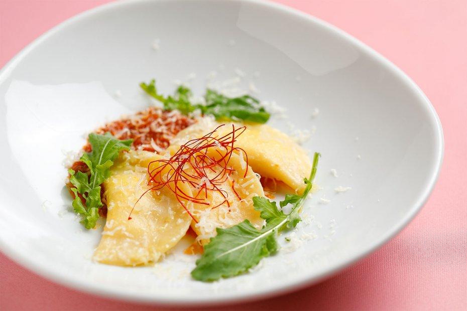 """モチモチ食感の自家製パスタ、メッツァルーナとはイタリア語で""""半月""""の意味。玉ねぎの甘みを感じるトマトソースを絡めて"""